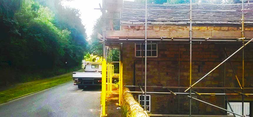 close up side view of simple builders scaffolding erected around a rural country house