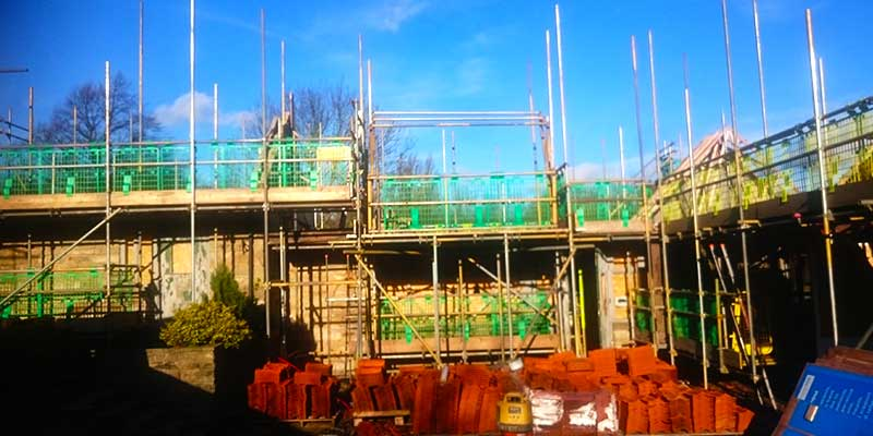 a very large scale building site with part buildings surrounded by high scaffolding supporting builders working