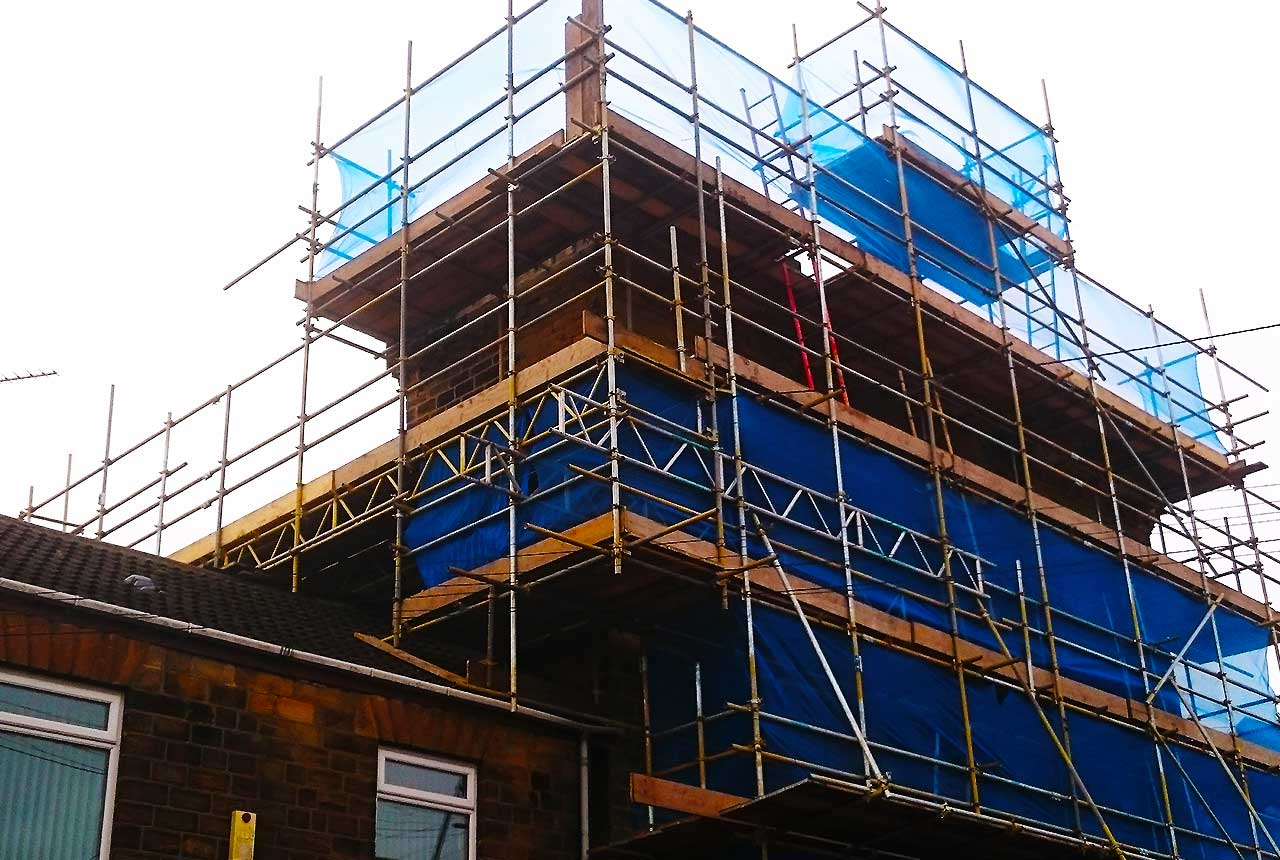 distance view of a sheffield domestic brick built home part way through a lost conversion wrapped in scaffold allowing tradesmen to work