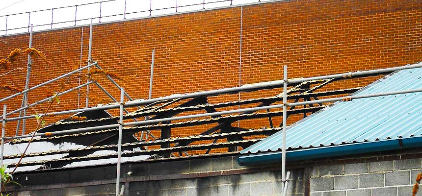 two scaffolders repairing damaged scaffolding around a chesterfield factory