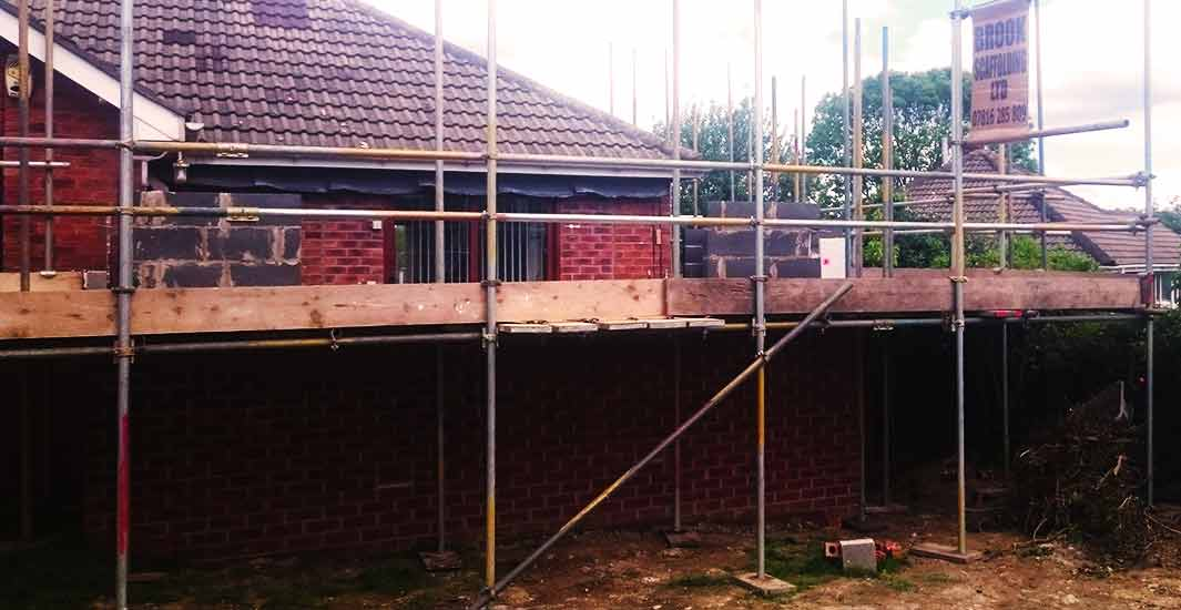 distance view of brook scaffoldings home scaffolders erecting scaffold around a rotherham brick built residential house