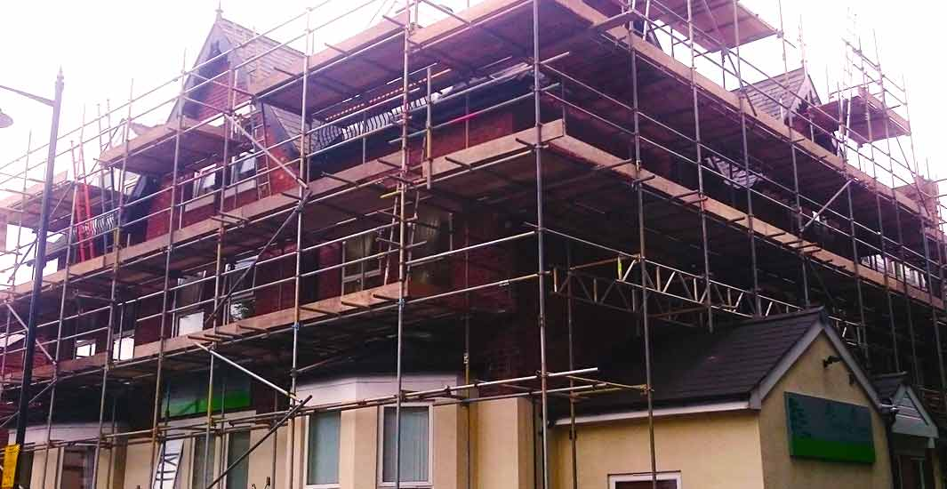 distance photo of a scaffold expert inspecting a building with scaffold erected all the way around a large new build sheffield property