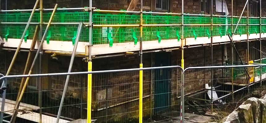 distance view of brooks sheffield scaffolders working hard erecting scaffold on a commercial property conmvesion
